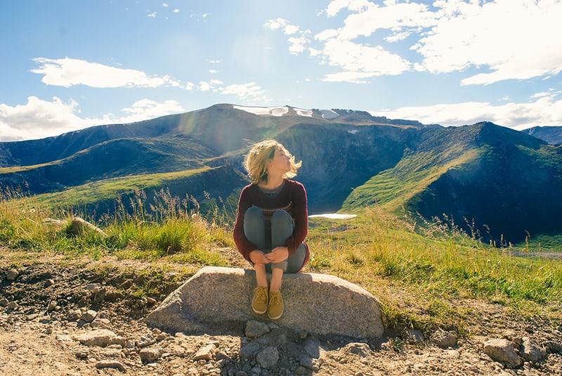 eine Frau, die in der Natur auf dem Felsen sitzt und nachdenkt