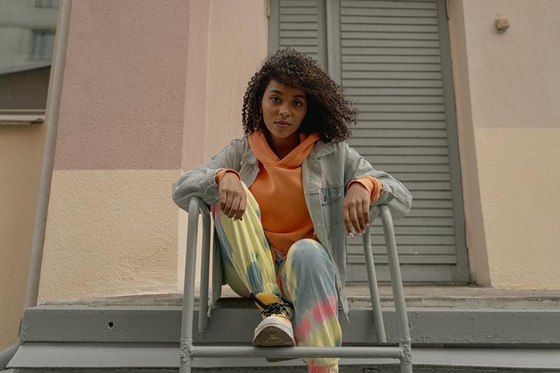 eine Frau sitzt auf der Leiter in der Nähe des Gebäudes