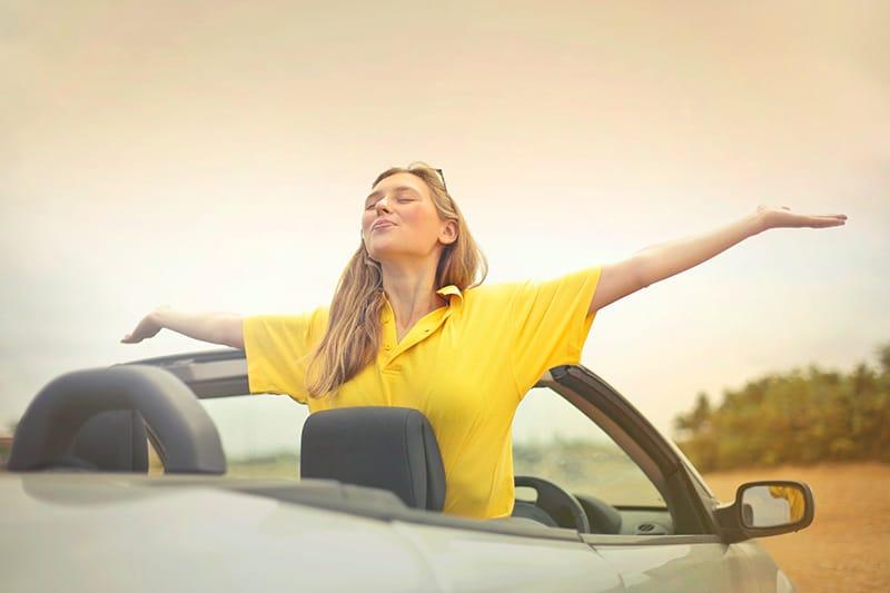 Eine Frau sitzt im Auto und breitet die Arme aus, während sie zum Himmel schaut