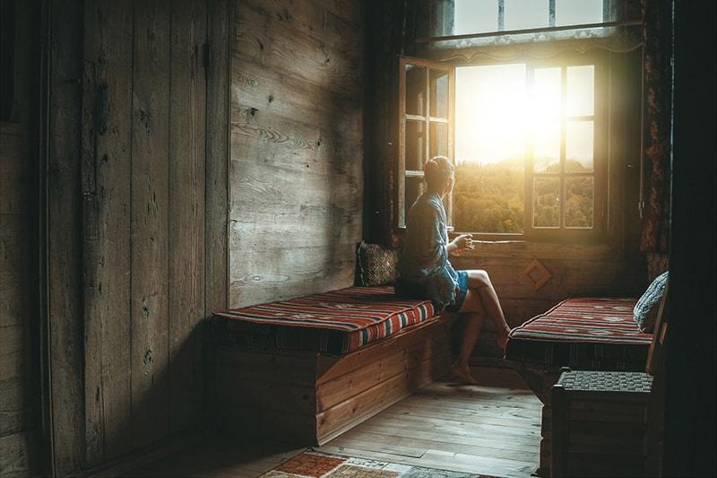 eine Frau, die neben einem Fenster sitzt und morgens den Sonnenaufgang beobachtet