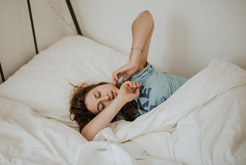 eine Frau, die im Bett aufwacht