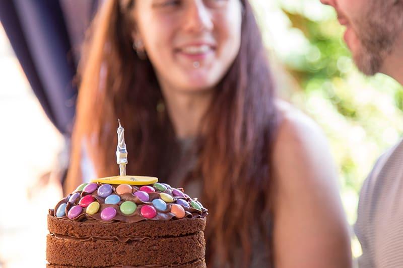 eine Geburtstagstorte mit Süßigkeiten vor einem Mann und einer Frau