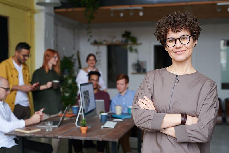 eine Geschäftsfrau, die vor ihrem Team im Besprechungsraum steht