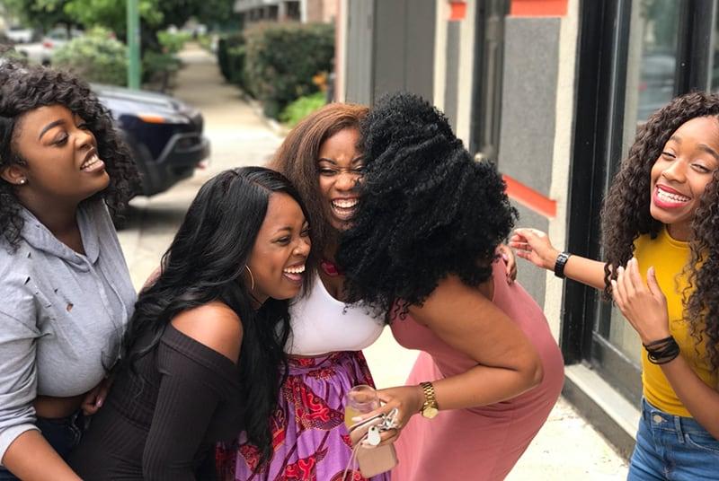 eine Gruppe lachender Freundinnen, die auf dem Bürgersteig stehen