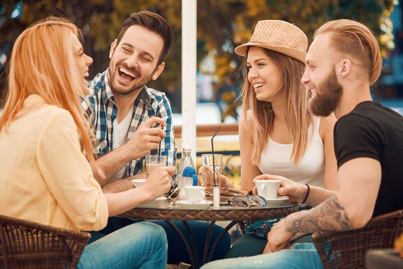 Eine Gruppe von Freunden lacht und scherzt, während sie im Café sitzen