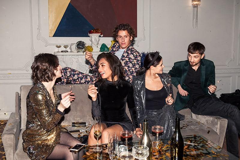 Eine Gruppe von Freunden sitzt auf der Couch auf der Party