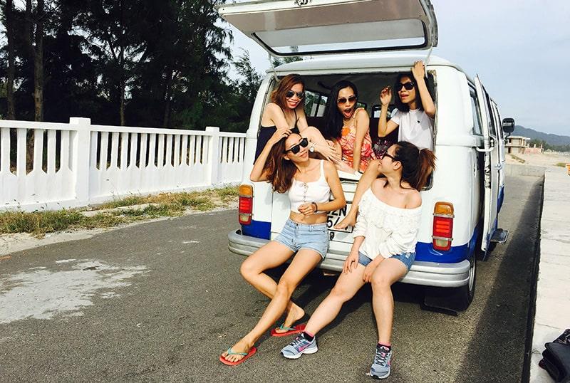 eine Gruppe von Freundinnen, die im Kofferraum des Autos sitzen und zusammen lachen