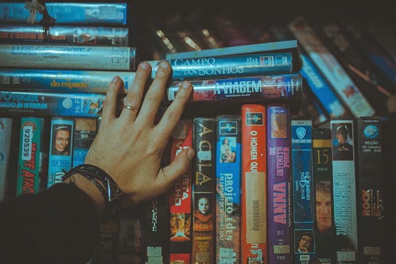 eine Person, die VHS-Bänder berührt, die im Regal sortiert sind