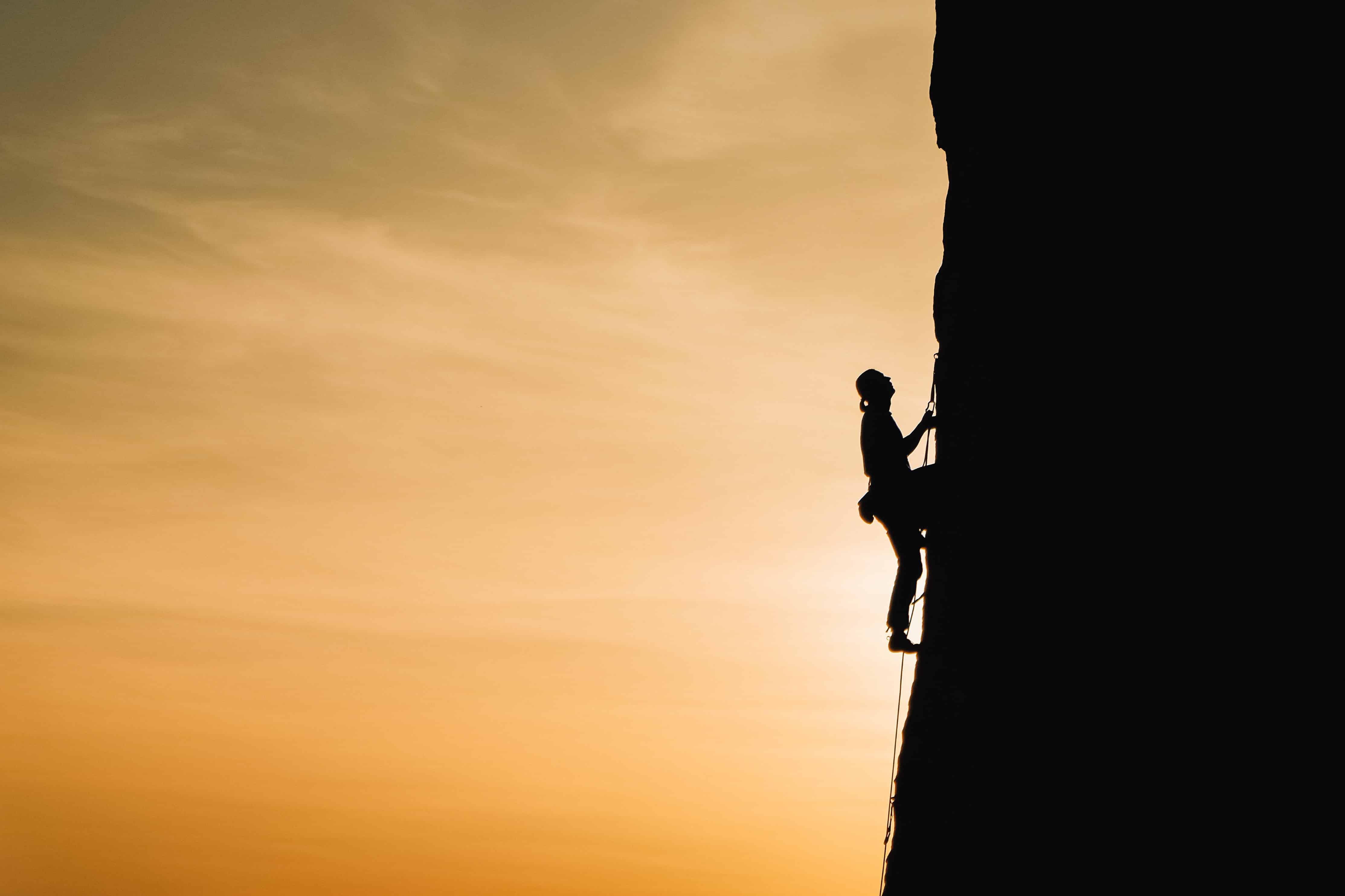 eine Person, die während des Sonnenuntergangs auf einem Felsen klettert