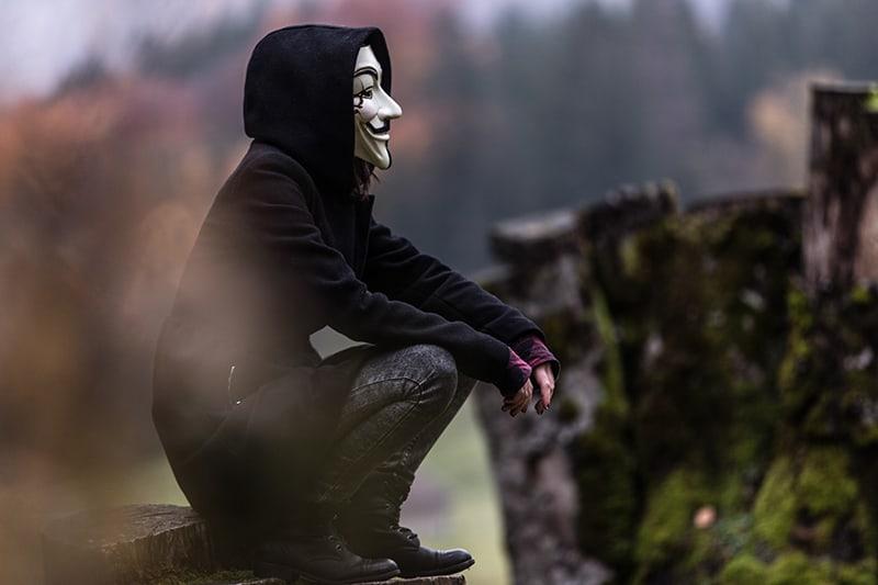 eine Person in einem schwarzen Kapuzenpulli und einer gruseligen Gesichtsmaske, die auf dem Boden sitzt