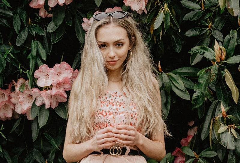 eine blonde Frau mit langen Haaren, die nahe dem Blumenbaum steht