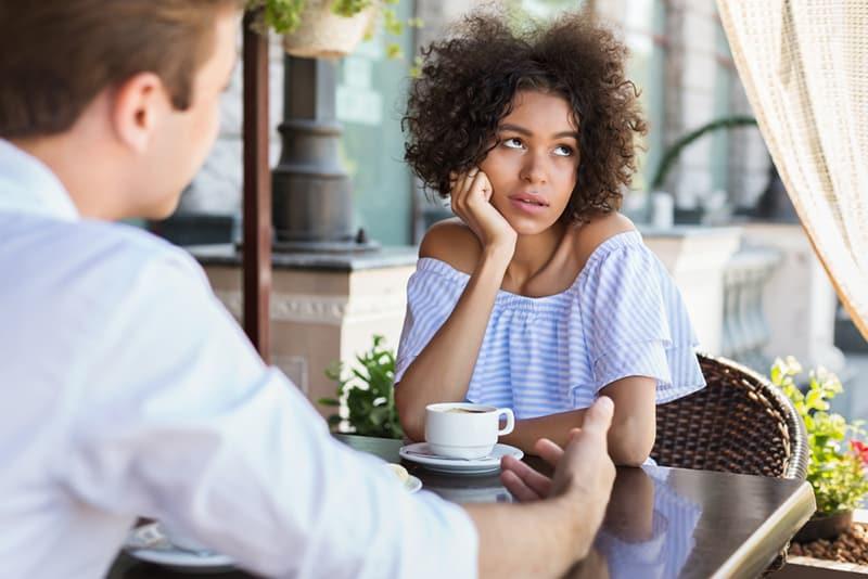 eine desinteressierte Frau, die beiseite schaut, während sie mit einem Mann an einem Blind Date sitzt