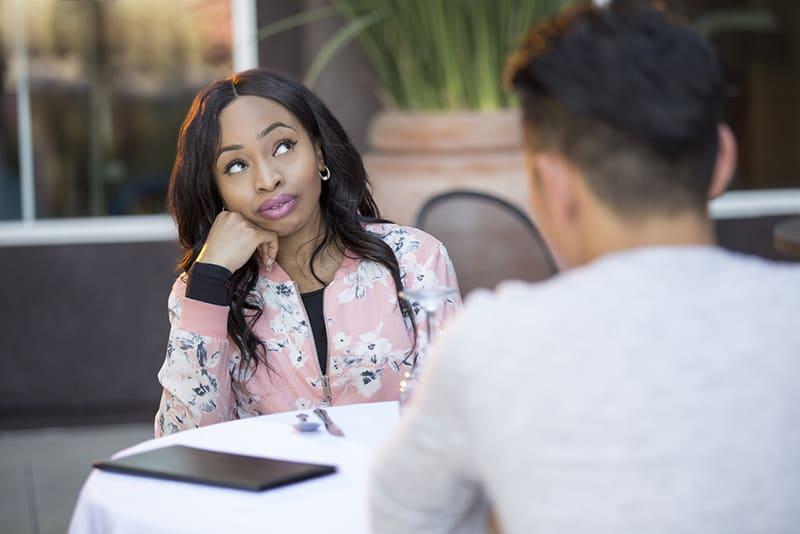 eine desinteressierte Frau, die mit einem Mann im Café an einem Date sitzt
