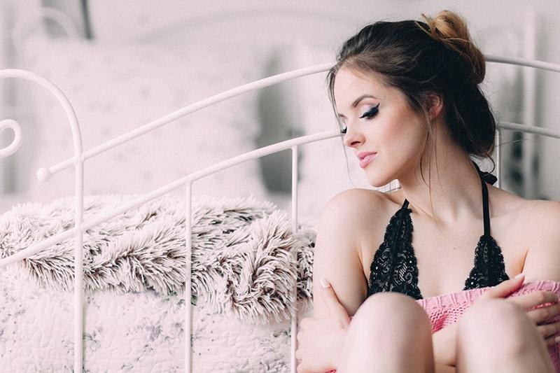 eine einsame Frau, die neben dem Bett sitzt und nach unten schaut