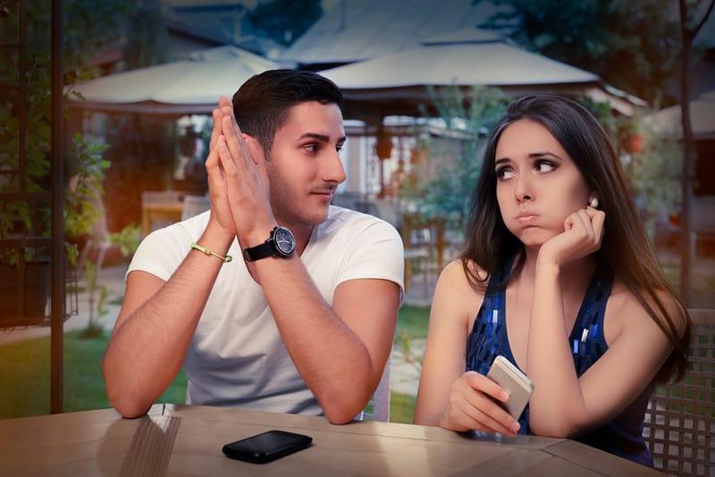 eine enttäuschte Frau, die einen Mann ansieht, der neben ihr sitzt und sich ansieht