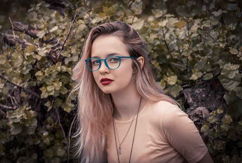 eine ernste Frau mit Brille, die in der Nähe des Busches steht