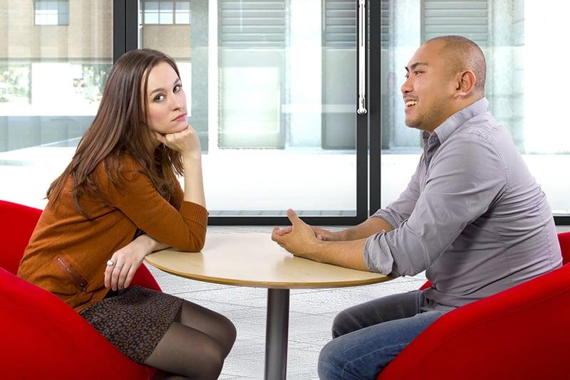 eine gelangweilte Frau, die mit einem lächelnden Mann auf einem Date sitzt