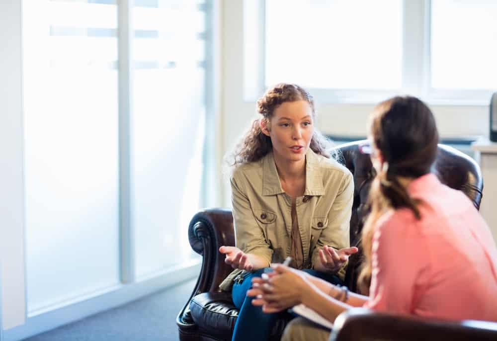 eine junge rothaarige Frau in einer Sitzung mit einem Psychologen