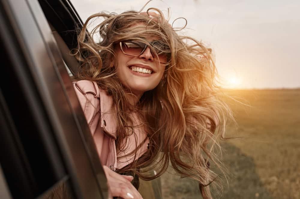 eine lächelnde Blondine mit Brille, die sich während der Fahrt aus einem Autofenster lehnt