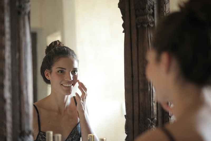 eine lächelnde Frau, die Creme auf Gesicht vor dem Spiegel aufträgt