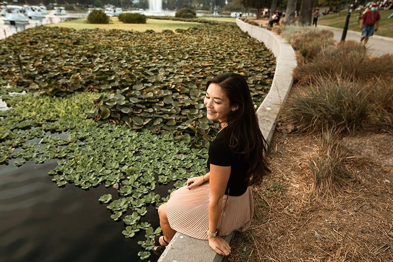 eine lächelnde Frau, die allein in der Nähe des Sees im Park sitzt