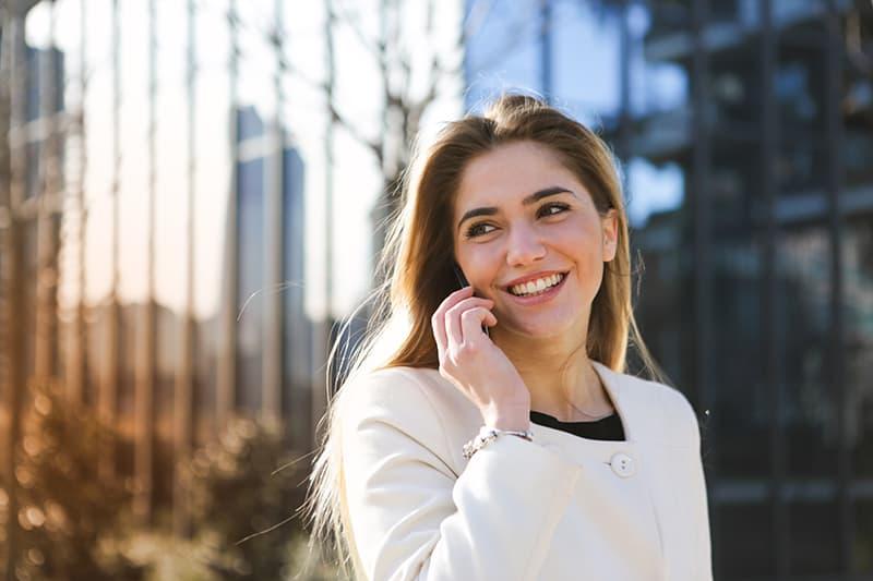 eine lächelnde Frau, die auf dem Smartphone spricht, während sie draußen steht