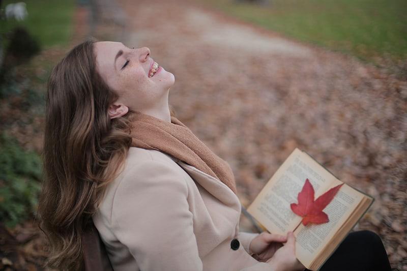eine lächelnde Frau, die ein Buch hält, während sie im Park sitzt