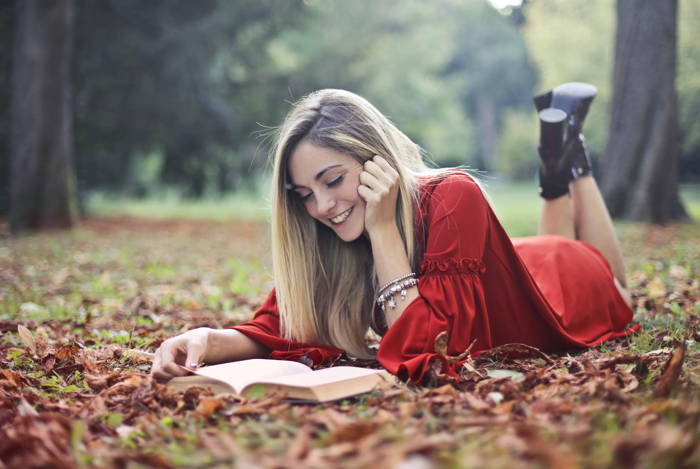 eine lächelnde Frau, die ein Buch liest, während sie auf getrockneten Blättern auf dem Boden liegt