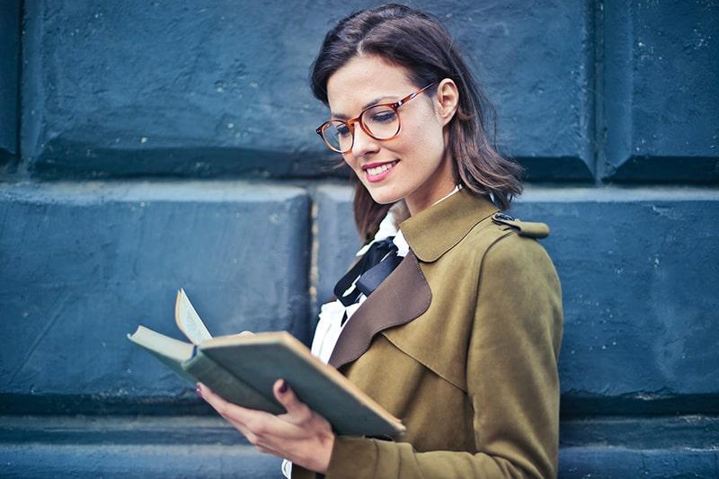 eine lächelnde Frau, die ein Buch liest, das nahe der blauen Wand steht