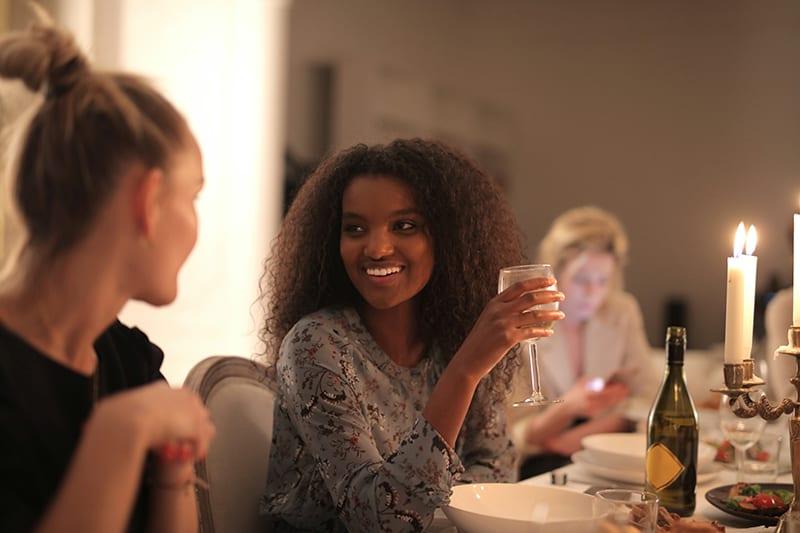 eine lächelnde Frau, die ein Glas Wein hält, während sie mit einer Freundin spricht