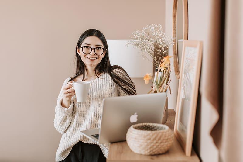 eine lächelnde Frau, die eine weiße Tasse hält, die nahe dem Laptop steht