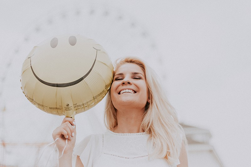 Eine lächelnde Frau hielt einen Ballon mit einem Smiley darauf und schloss die Augen