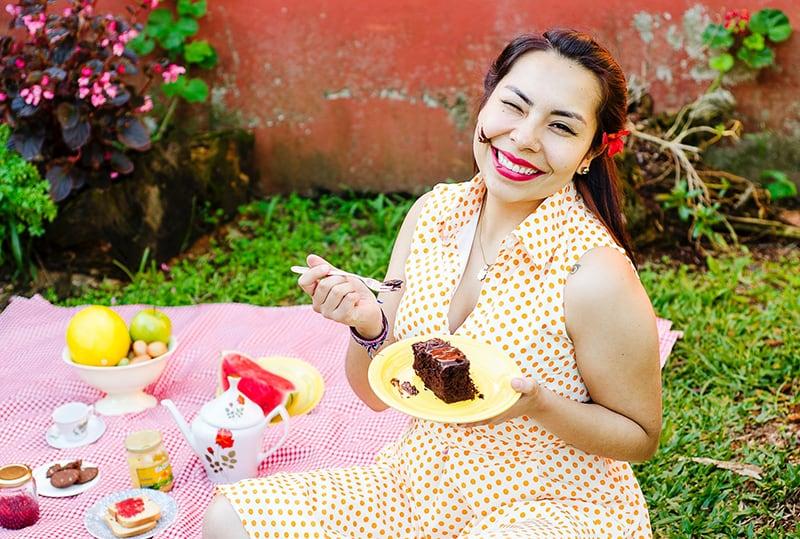eine lächelnde Frau, die einen Kuchen auf einem Picknick isst