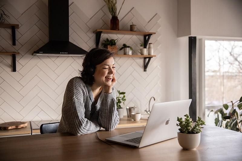 eine lächelnde Frau, die einen Videoanruf über Laptop in der Küche sitzt