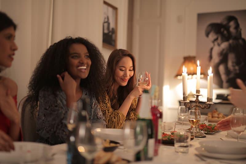 eine lächelnde Frau, die während eines Abendessens mit ihren Freundinnen spricht