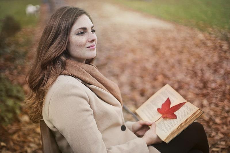 eine lächelnde Frau, die nachdenklich aussieht und ein Buch hält, während sie im Park sitzt
