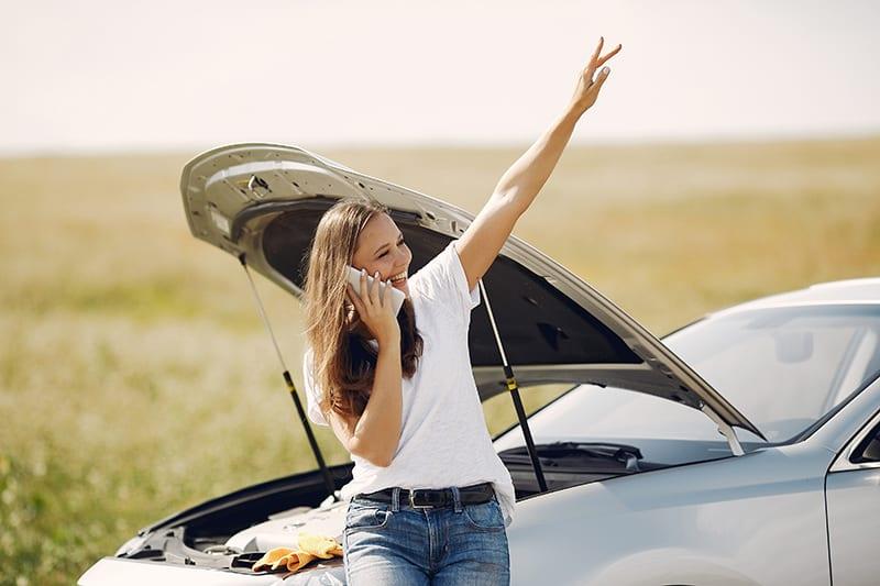 eine lächelnde Frau, die sich auf das kaputte Auto stützt, während sie einen Anruf hat