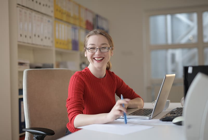 eine lächelnde Frau, die vor einem Laptop im Büro sitzt