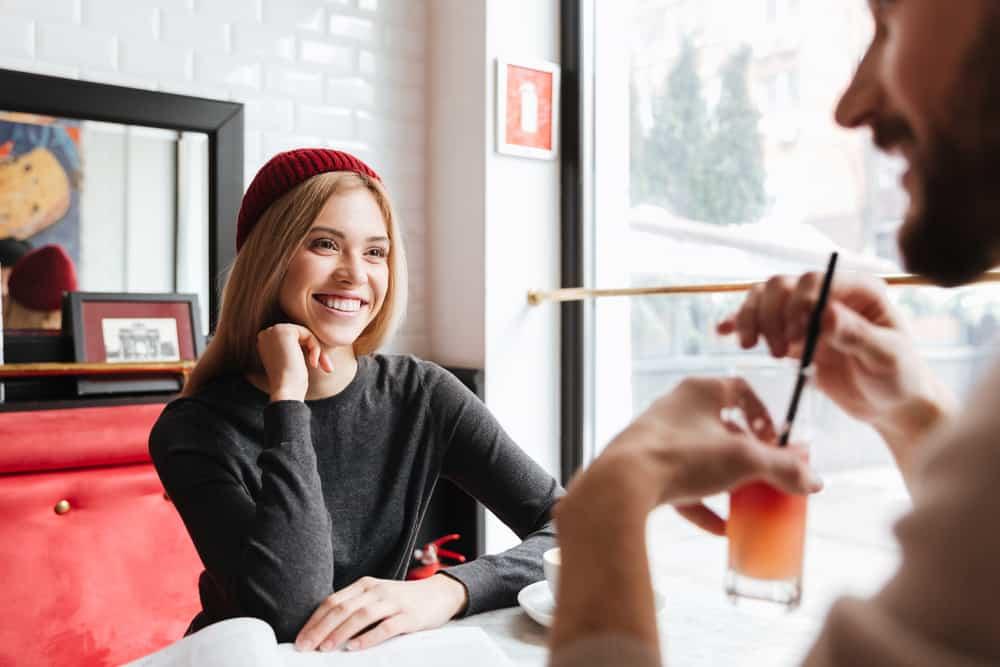 eine lächelnde Frau mit einer roten Mütze, die mit einem Mann in einem Café spricht