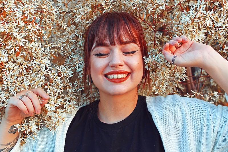 eine lächelnde Frau mit geschlossenen Augen, umgeben von Blumen