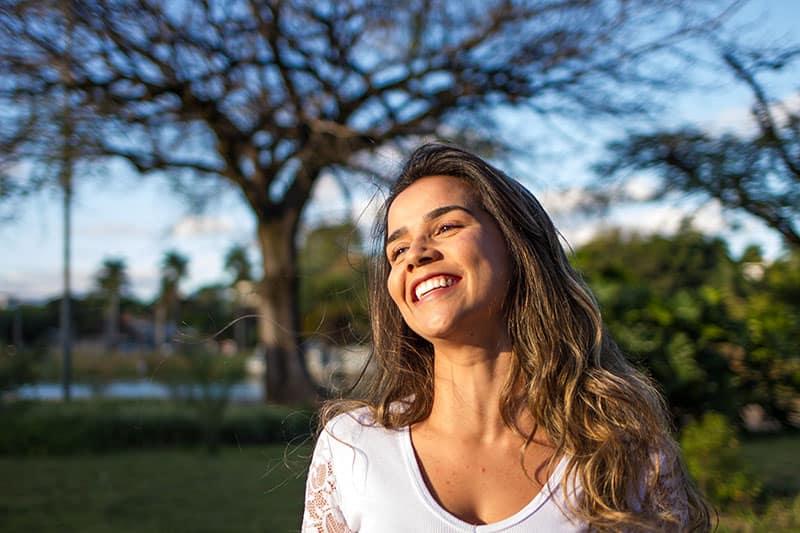 eine lächelnde Frau mit langen blonden Haaren, die im Park stehen