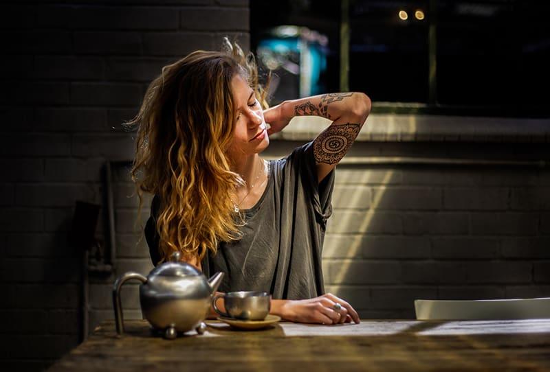 eine müde Frau, die abends neben einem Tisch sitzt