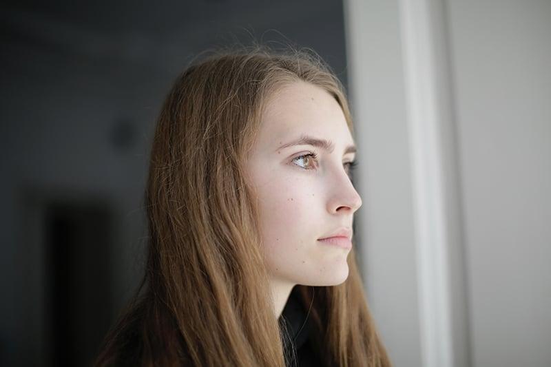 eine nachdenkliche Frau, die am Fenster steht und durch das Fenster schaut
