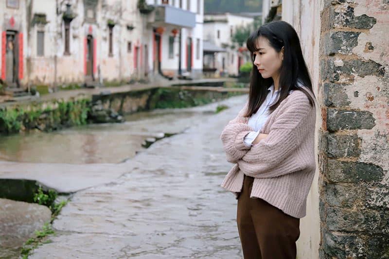eine nachdenkliche Frau, die auf dem Bürgersteig nahe der Mauer steht
