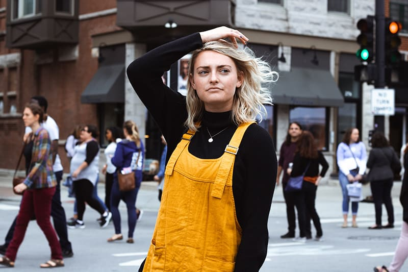 eine nachdenkliche Frau, die auf der Straße geht und ihre Haare berührt