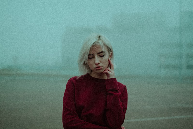 eine nachdenkliche Frau, die ihr Gesicht berührt, während sie in einem dichten Nebel steht