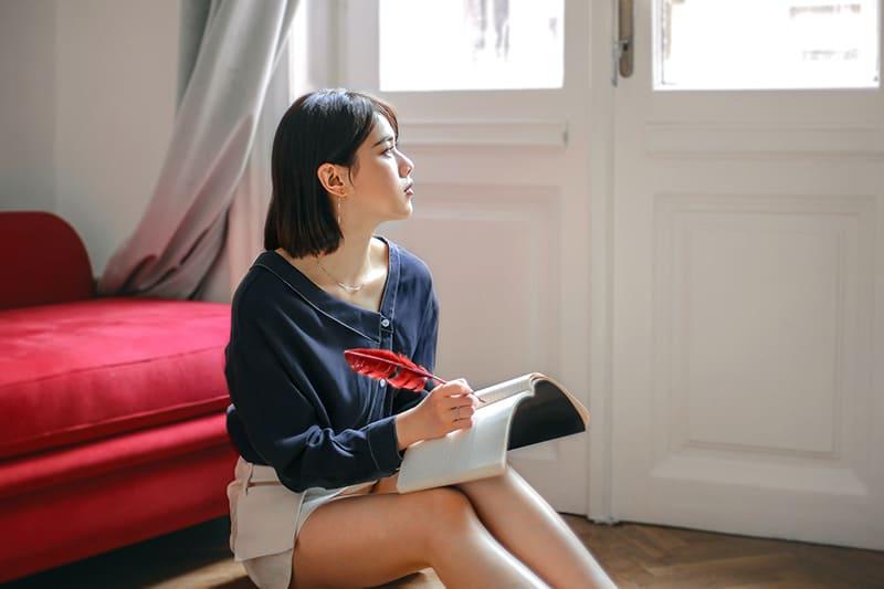 eine nachdenkliche Frau, die in ein Notizbuch schreibt, während sie auf dem Boden sitzt