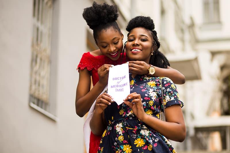 Eine stolze Frau umarmt ihre Freundin von hinten und hält eine Notiz