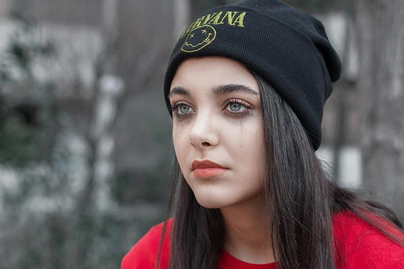 eine traurige Frau in einer schwarzen Mütze, die beiseite schaut