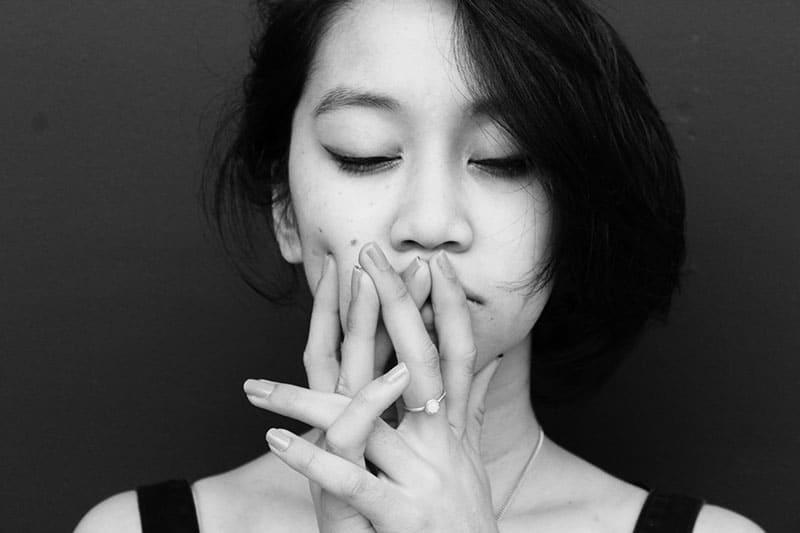 Eine traurige Frau mit geschlossenen Augen berührte ihr Gesicht mit den Handflächen